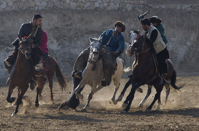 Afghan horse riders compete for the goat during a friendly buzkashi match on the outskirts of Kabul, Afghanistan, Thursday, January 15, 2015. Buzkashi is a traditional and the national sport of Afghanistan, where players compete to place a goat carcass into a goal circle. It was banned during the Taliban rule. (Photo by Massoud Hossaini/AP Photo)