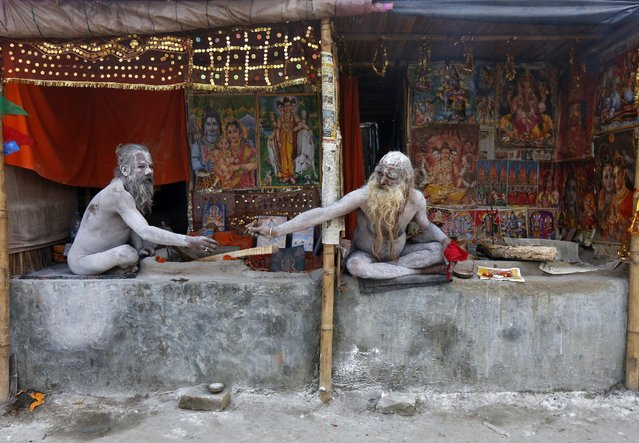 "Naga Sadhus or Hindu holy men, smeared with ash, pass on a chillum to smoke inside their makeshift camps near the confluence of the river Ganges and the Bay of Bengal, ahead of the ""Makar Sankranti"" festival at Sagar Island, south of Kolkata, India, January 13, 2016. Hindu monks and pilgrims are making their annual trip to Sagar Island for the one-day festival of ""Makar Sankranti"" on Friday. (Photo by Rupak De Chowdhuri/Reuters)"