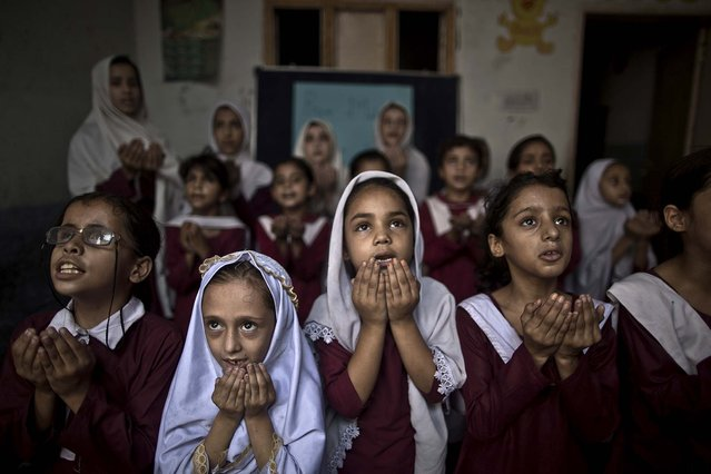 Schoolchildren chant prayers during a special class to recognize the anniversary of Malala Yousufzai's shooting by the Taliban, at a school in Rawalpindi, Pakistan, on Oktober 9, 2013. One year after a Taliban bullet tried to silence Malala's demand for education, she has published a book and is a contender for the Nobel Peace Prize. But the militants threaten to kill her should she dare return home from Britain to Pakistan, and the principal at her old school says that as Malala's fame has grown, so has fear in her classrooms. (Photo by Muhammed Muheisen/Associated Press)