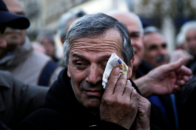 A Greek pensioner wipes his face with a fake euro banknote during a demonstration against government policies affecting pensioners in Athens, Greece, December 15, 2016. (Photo by Alkis Konstantinidis/Reuters)