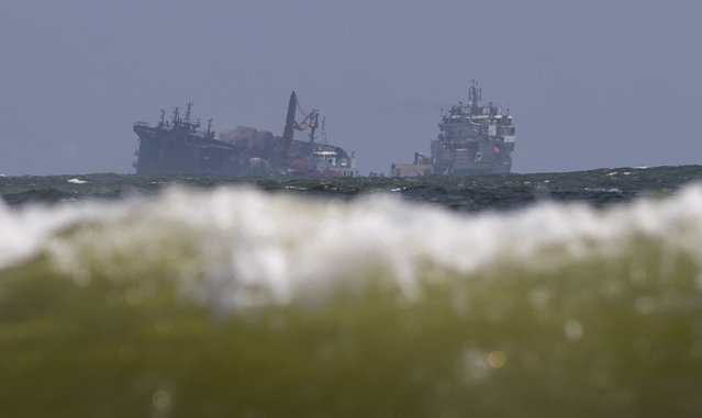 The MV X-Press Pearl, left, is pulled by a navel vessel at Kapungoda, where it is anchored off Colombo port on the outskirts of Colombo, Sri Lanka, Wednesday, June 2, 2021. Salvage experts were attempting to tow the fire-stricken container ship that had been loaded with chemicals into the deep sea as the vessel started to sink Wednesday off Sri Lanka's main port, officials said. Water submerged the MV X-Press Pearl's quarterdeck a day after firefighters extinguished a blaze that had been burning for 12 days. (Photo by Eranga Jayawardena/AP Photo)