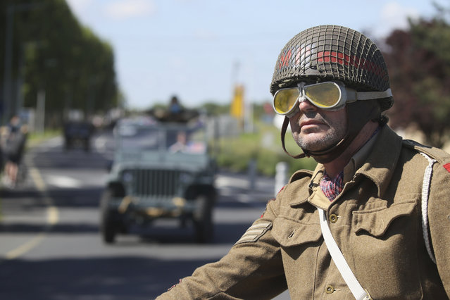 World War II history enthusiasts parade in WWII vehicles in Ouistreham, Normandy, Saturday June, 5 2021 on the eve of 77th anniversary of the assault that helped bring an end to World War II. While France is planning to open up to vaccinated visitors starting next week, that comes too late for the D-Day anniversary. So for the second year in a row, most public commemoration events have been cancelled. A few solemn ceremonies have been maintained, in the presence of dignitaries and a few guests only. (Photo by David Vincent/AP Photo)