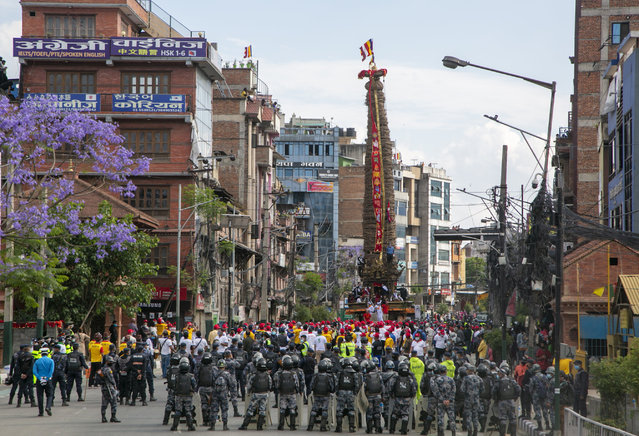 Policemen stand guard as Nepalese devotees pull a chariot during the Rato Machindranath chariot festival in Lalitpur, Nepal, Saturday, May 15, 2021. A truncated version of a Hindu chariot festival took place in Nepal's capital on Saturday amid strict COVID-19 restrictions, following an agreement between organizers and authorities that prevented a repeat of violent confrontations between police and protesters at last year's festival. (Photo by Niranjan Shrestha/AP Photo)