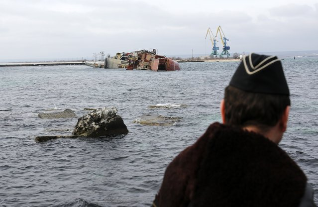 "In this Thursday, March 6, 2014 file photo a Ukrainian Navy officer looks at the scuttled decommissioned Russian vessel ""Ochakov"" from the Black Sea shore outside the town of Myrnyi, western Crimea. (Photo by Darko Vojinovic/AP Photo)"