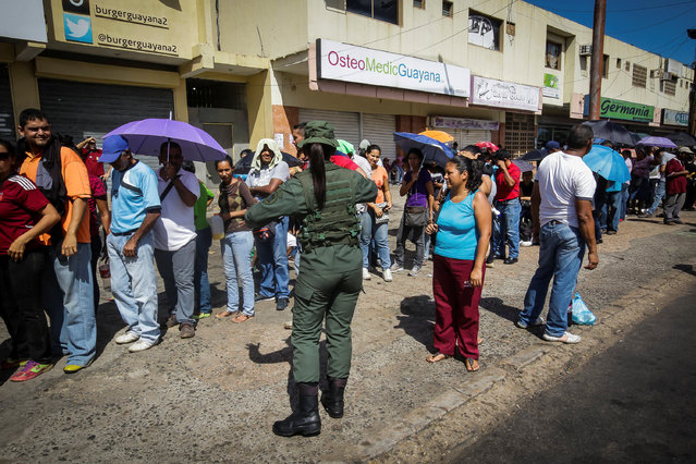 A Venezuelan soldier controls the crowd as people queue to buy goods from a food wholesaler in Ciudad Bolivar, Venezuela December 19, 2016. (Photo by William Urdaneta/Reuters)