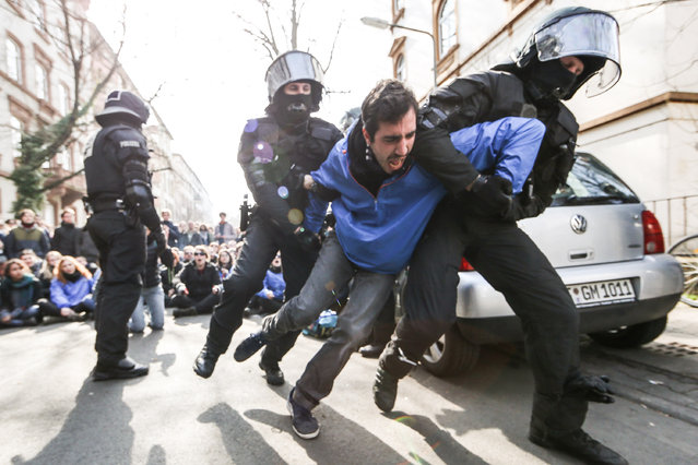 Riot police carry away an activist during a demonstration organized by the Blockupy movement to protest against the policies of the European Central Bank (ECB) after the ECB officially inaugurated its new headquarters earlier in the day on March 18, 2015 in Frankfurt, Germany. (Photo by Simon Hofmann/Getty Images)