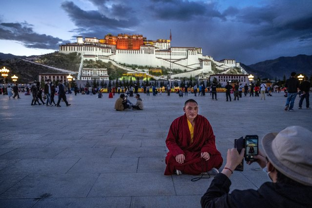 A Tibetan Buddhist monk has his photo taken in front of the Potala Palace, a UNESCO heritage site, as he visits the square, on June 1, 2021 in Lhasa, Tibet Autonomous Region, China. (Photo by Kevin Frayer/Getty Images)