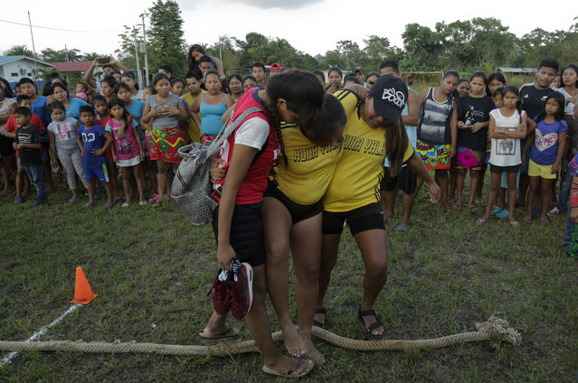 In this November 25, 2018 photo, an injured Guna woman is aid by her teammates after the tug-of-war competition of the second edition of the Panamanian indigenous games in Piriati, Panama. Events such as archery, swimming, wrestling and running are also a part of the games. (Photo by Arnulfo Franco/AP Photo)