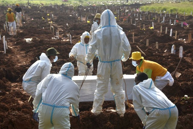 Gravediggers bury a coffin of a Covid-19 coronavirus victim at a cemetary in Bekasi on July 4, 2021. (Photo by Rezas/AFP Photo)