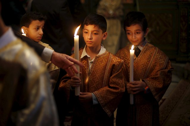 Palestinian boys hold candles as they attend Orthodox Christian Palm Sunday mass at the Saint Porfirios church in Gaza City April 5, 2015. (Photo by Suhaib Salem/Reuters)