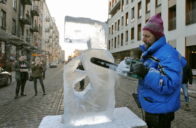 Artist Jan Kubicki carves in ice on a closed section of Zabkowska street, in Warsaw, Poland, Saturday, January 7, 2017, as the temperature is minus 10 degree Celsius (14 degree Fahrenheit). At least 10 people have died of the cold in Poland in the past days, according to officials. (Photo by Alik Keplicz/AP Photo)