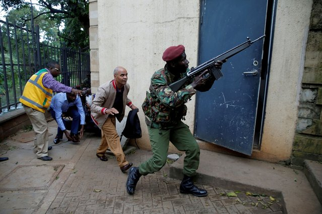 A member of security forces keeps guard as people are evacuated at the scene where explosions and gunshots were heard at the Dusit hotel compound, in Nairobi, Kenya January 15, 2019. (Photo by Thomas Mukoya/Reuters)