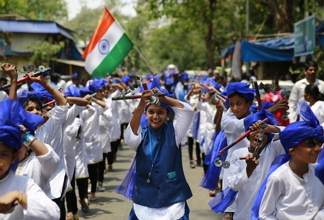 Young Indians dance during a procession to mark the birth anniversary of Bhim Rao Ambedkar in Mumbai, India, Tuesday, April 14, 2015. Ambedkar, an untouchable, or Dalit, and a prominent Indian freedom fighter, was the chief architect of the Indian Constitution, which outlawed discrimination based on caste. (Photo by Rafiq Maqbool/AP Photo)