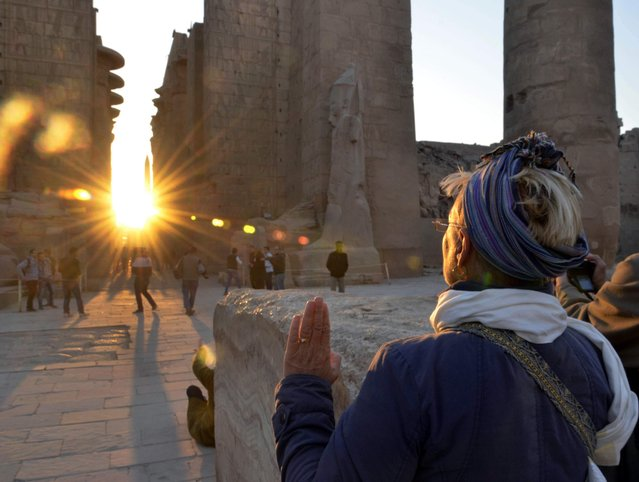 A tourist makes a sunrise visit to the temple of Karnak on the day of the winter solstice in Luxor, 510 kilometers (320 miles) south of Cairo, Egypt, Saturday, December 21, 2013. Tourism, which accounts for nearly 20 percent of Egypt's foreign currency revenues, has been hard hit by the past three years of turmoil. Government officials have been campaigning to regain some of the European, American and Asian tourism that was suspended following violence this summer. (Photo by Ibrahim Zayed/AP Photo)