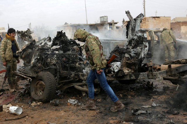 A rebel fighter walks near damaged vehicles after a car bomb explosion in Jub al Barazi east of the northern Syrian town of al-Bab, Syria January 15, 2017. (Photo by Khalil Ashawi/Reuters)