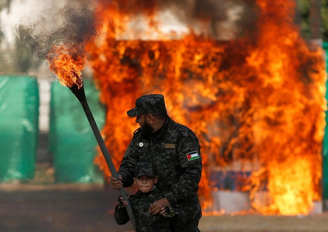 A Palestinian man helps a boy set fire to an Israeli flag during a graduation ceremony for Hamas security forces in Gaza City on January 22, 2017. (Photo by Mahmud Hams/AFP Photo)