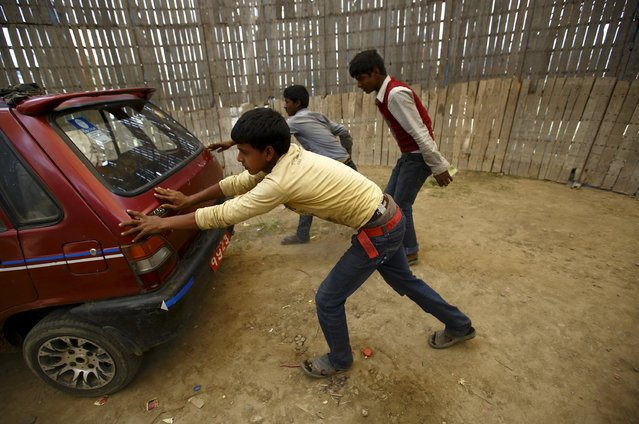 "Boys try to push start a car inside the ""Well of Death"" attraction during a fair in Bhaktapur April 20, 2015. (Photo by Navesh Chitrakar/Reuters)"