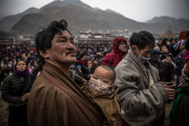 An Ethnic Tibetan man holding a child looks at a huge thangka (sacred painting on cloth) depicting Buddha during Monlam Great Prayer Festival, at Labrang Monastery, in Xiahe, an ethnically-Tibetan town in Gansu province, China, 17 February 2019. The Monlam Great Prayer Festival starts three days after the Tibetan New Year and is held for almost two weeks. The festival is considered the most important event for Tibetan Buddhists. Every year thousands of visitors and worshipers gather at Labrang Monastery to mark Monlam together with the Tibetan Buddhist monks. Labrang Monastery is the largest monasteries of the Yellow Hat sect of Tibetan Buddhism and home to the largest number of monks outside of the Tibet Autonomous Region. The monastery was founded in 1709. (Photo by Roman Pilipey/EPA/EFE)