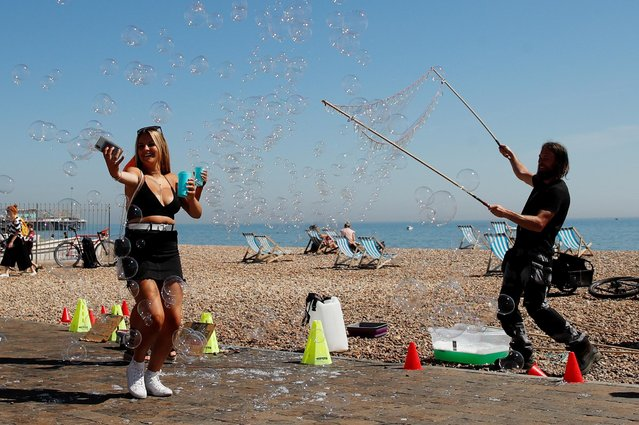 People play with bubbles on the beach in Brighton, following the outbreak of the coronavirus disease (COVID-19), Brighton, Britain, May 21, 2020. (Photo by Matthew Childs/Reuters)