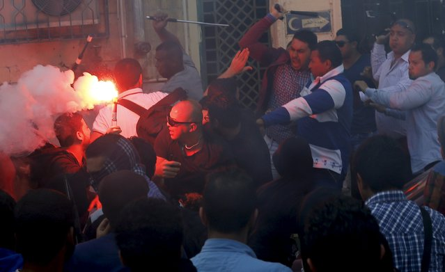 Administrative security personnel (R) clash with Cairo University students with a light flare who are supporters of the Muslim Brotherhood and ousted President Mohamed Mursi during a protest against the military and interior ministry at the university's campus in Giza, on the outskirts of Cairo, April 19, 2015. (Photo by Amr Abdallah Dalsh/Reuters)
