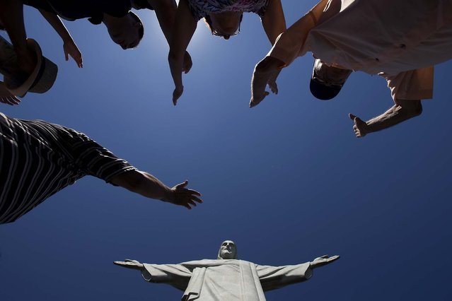 Visitors raise their arms to pray below the Christ Redeemer statue on January 21, 2014. (Photo by Felipe Dana/Associated Press)
