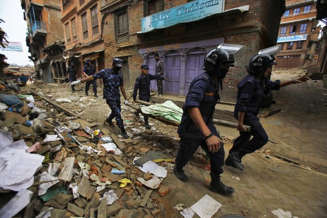 Nepalese rescue team carry on a stretcher the body of a victim recovered from the debris of a building that collapsed after an earthquake in Bhaktapur, near Kathmandu, Nepal, Sunday, April 26, 2015. (Photo by Niranjan Shrestha/AP Photo)
