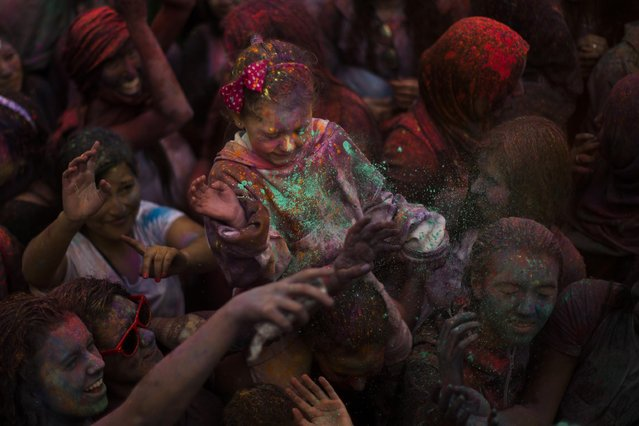 Revelers throw coloured powder to the crowd during a Holi Festival in Madrid, Spain, Sunday, April 26, 2015. (Photo by Andres Kudacki/AP Photo)