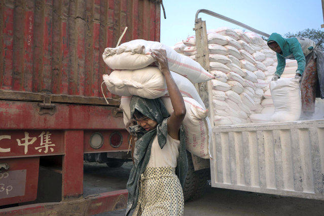 A 14 year-old Myanmar girl carries three bags of powdered-limestone to load in to a boat on the bank of Ayeyarwaddy River, on International Women's Day in Mandalay, Myanmar, Tuesday, March 8, 2016. Migrant workers living along Ayeyarwaddy riverbank earn bout 5000 Kyats (US Dollar 4) a day for loading and unloading goods. (Photro by Hkun Lat/AP Photo)