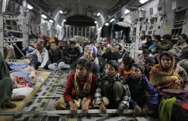 Survivors of Saturday's earthquake hold on to a cable as a military takes off with evacuees from Kathmandu to New Delhi during a midnight rescue mission by Indian Air Force, in Kathmandu, Nepal, Wednesday, April 29, 2015. (Photo by Altaf Qadri/AP Photo)