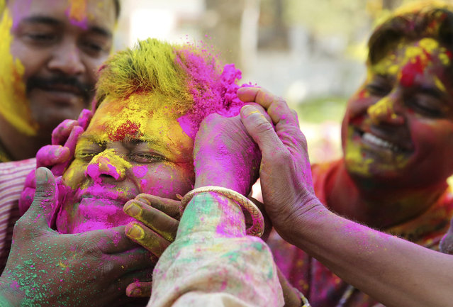 An Indian man has colored powder smeared on his face during celebrations marking Holi, the Hindu festival of colors, in Allahabad, India, Wednesday, March 20, 2019. Holi also marks the advent of spring season. (Photo by Rajesh Kumar Singh/AP Photo)