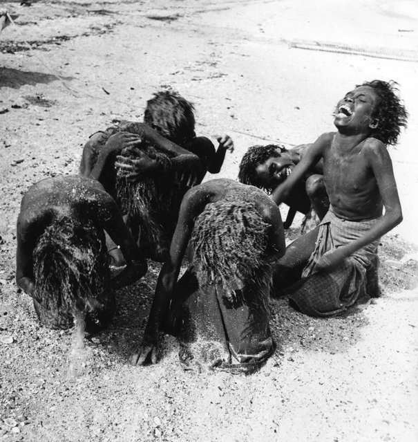 1st January 1950:  Aboriginal women washing their hair with sand at Arnhem land in the Northern Territory of Australia.  (Photo by Three Lions/Getty Images)