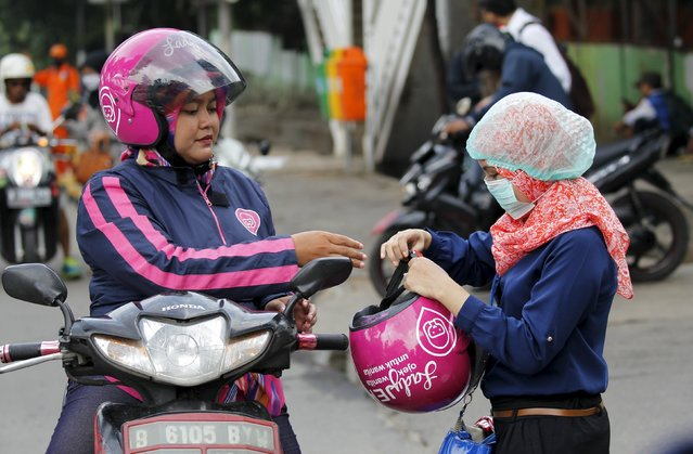 A Ladyjek driver (L) gives a helmet to her customer before a riding motorcycle at a street in Jakarta, January 11, 2016. Picture taken January 11, 2016. (Photo by Garry Lotulung/Reuters)