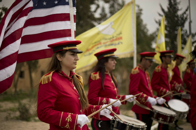 A military band performs ahead of a ceremony at al-Omar Oil Field marking the U.S.-backed Syrian Democratic Forces (SDF) capture of Baghouz, Syria, after months of fighting to oust Islamic State militants Saturday, March 23, 2019.  The elimination of the last Islamic State stronghold in Baghouz brings to a close a grueling final battle that stretched across several weeks and saw thousands of people flee the territory and surrender in desperation, and hundreds killed. (Photo by Maya Alleruzzo/AP Photo)