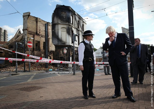London Mayor Boris Johnson stands with Police Superintendent Jo Oakley near burnt out Reeves Corner furniture store on August 9, 2011 in Croydon, England