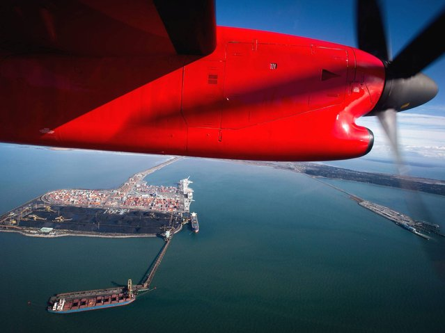 A National Aerial Surveillance Program flight flies over Deltaport as a ship is loaded with coal at Westshore Terminals in Delta, British Columbia, on Wednesday, February 19, 2014. (Photo by Darryl Dyck/AP Photo/The Canadian Press)