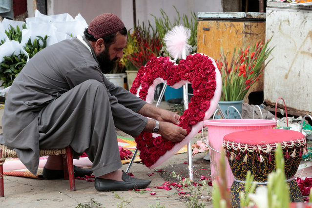 A man arranges a heart-shaped bouquet at a flower market in Islamabad, Pakistan February 14, 2017. (Photo by Caren Firouz/Reuters)