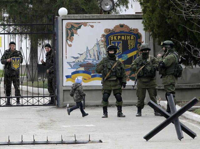 A boy runs by as Ukrainian soldiers look on from behind gates as Russian soldiers guard the gate of an infantry base in Perevalne, Ukraine, Tuesday, March 4, 2014. (Photo by Darko Vojinovic/AP Photo)