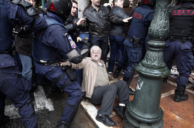 An anti-austerity protester sits on the ground during scuffles with police officers following a demonstration by several hundreds of protesters, some of them from the communist-affiliated trade union PAME, in Athens March 6, 2014. (Photo by Alkis Konstantinidis/Reuters)
