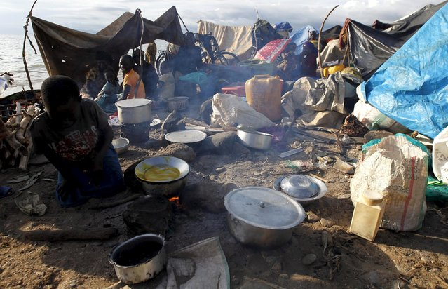 A Burundian refugee prepares food near their makeshift shelters as they gather on the shores of Lake Tanganyika in Kagunga village in Kigoma region in western Tanzania, to wait for MV Liemba to transport them to Kigoma township, May 17, 2015. (Photo by Thomas Mukoya/Reuters)