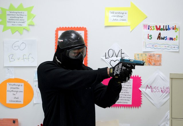 "A student prepares to confront a ""gunman"" in a middle school classroom during an Active Shooter Response course offered by TAC ONE Consulting in Denver April 2, 2016. (Photo by Rick Wilking/Reuters)"