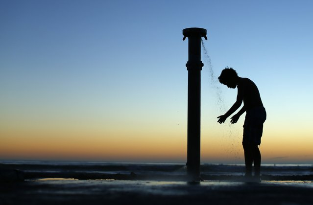 A boy showers off after sunset at the beach in Cardiff, California March 10, 2014. (Photo by Mike Blake/Reuters)
