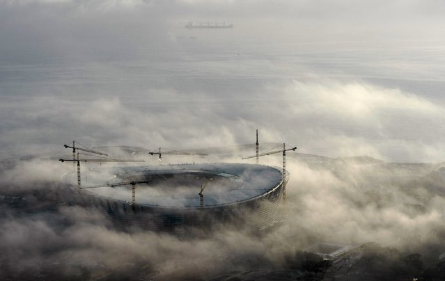 Early morning fog enshrouds Cape Town's Green Point 2010 FIFA Soccer World Cup Stadium, in this August 25, 2009 file photo. (Photo by Mike Hutchings/Reuters)