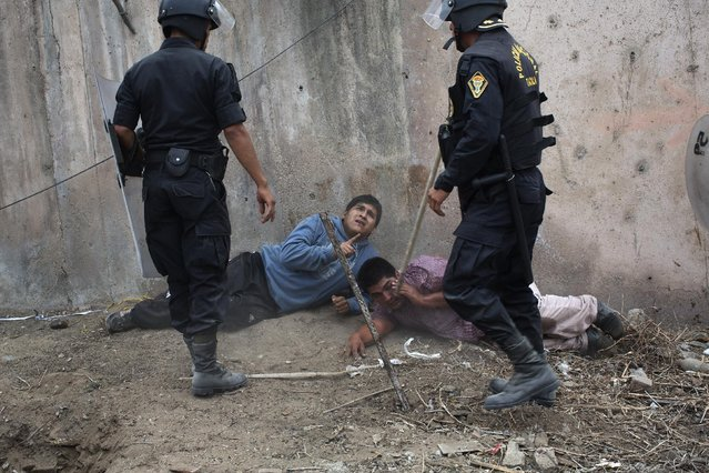 Riot police detain men during a land eviction in Lima Peru,Tuesday, May 19, 2015. On Monday hundreds of people squatted on land that according to the Ministry of Culture is an archaeological site. (Photo by Rodrigo Abd/AP Photo)