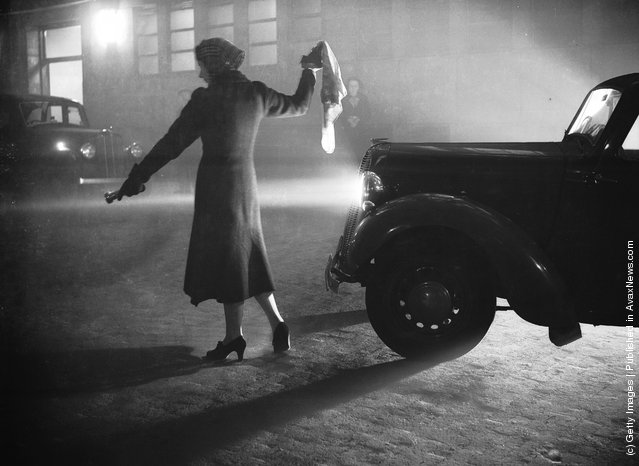1938: A woman leads a car through London's Regent's Park with a torch, during the thick fog with visibility reduced to a few yards