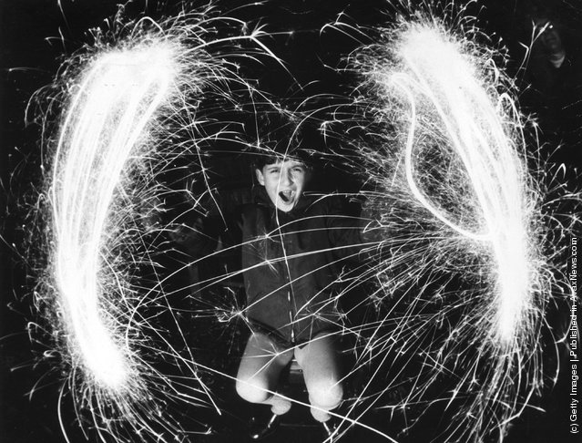 Fish eye lens gives a new angle on fireworks held by Marc Robert age 7 who is whirling sparklers but wearing gloves for safety, 1968
