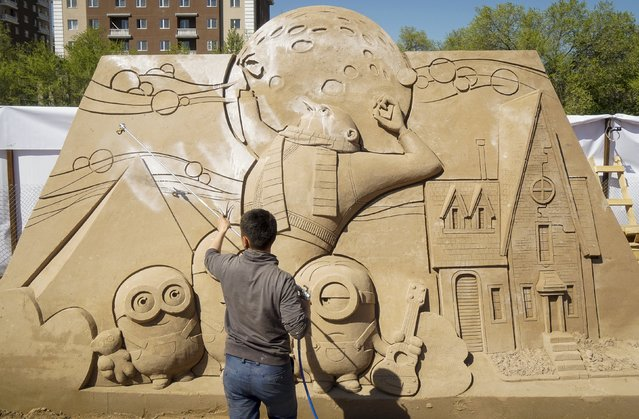 """A man sprays protective glue on a creation during the Sand Sculpture Festival """"Sand Fantasy"""" in Almaty, Kazakhstan, April 15, 2016. (Photo by Shamil Zhumatov/Reuters)"""
