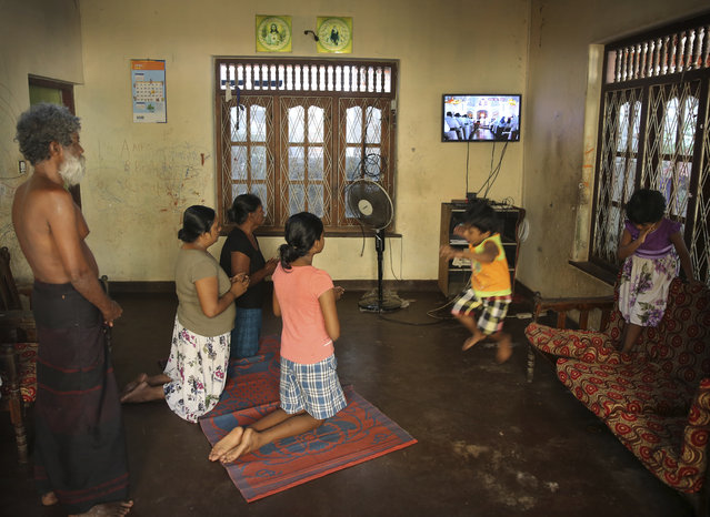 A Sri Lankan Christian catholic family prays as children play inside their home watching live transmission of Sri Lankan Archbishop Cardinal Malcolm Ranjith, in Negombo, Sri Lanka, Sunday, April 28, 2019. Sri Lanka's Catholics celebrated Sunday Mass in their homes by a televised broadcast as churches across the island nation shut over fears of militant attacks, a week after the Islamic State-claimed Easter suicide bombings killed over 250 people. (Photo by Manish Swarup/AP Photo)