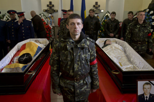 A Ukrainian soldier looks up standing between the coffins of Ukrainian soldier Sergey Kokurin, 35, right,  and Russian Cossack militiaman Ruslan Kazakov, 34, left, during their funeral in Simferopol, Crimea, Saturday, March 22, 2014. A few hundred mourners gathered to pay their last respects to two men who were shot dead earlier in the week. (Photo by Vadim Ghirda/AP Photo)