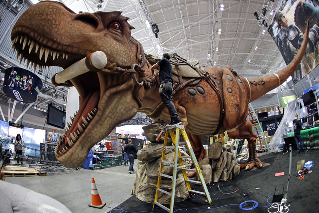 Joshua Patino stands on a ladder to put finishing touches on a giant dinosaur exhibit at PAX East in the Boston Convention and Expo Center, Thursday, April 21, 2016, in Boston. PAX East, an annual celebration of gaming culture, is expected to draw tens of thousands of visitors Friday through Sunday. It's a place where serious gamers can preview unreleased video games and devices, compete in tournaments, hear live music and meet others for whom gaming is a way of life. (Photo by Elise Amendola/AP Photo)