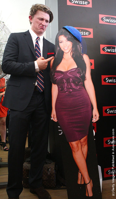 Race-goers pose with a cardboard cut-out of Kim Kardashian at the Swisse marquee during Emirates Stakes Day